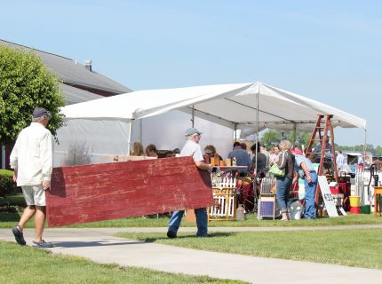 Shoppers carrying larger red barn door at the Shipshewana Antique & Vintage Market Festival in Indiana