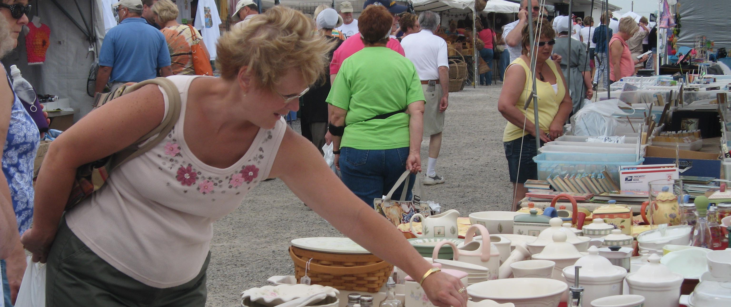 Lady looking at dishes at the Shipshewana Flea Market